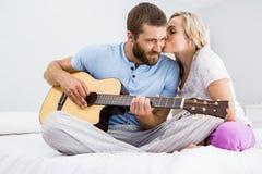 Bemannen Sie das Spielen der Gitarre während die Frau, die ihn auf Backe auf Bett küsst Stockfotos