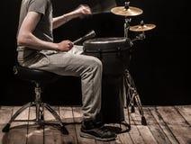 Bemannen Sie das Spielen einer der djembe Trommel und Becken auf einem schwarzen Hintergrund Lizenzfreies Stockfoto