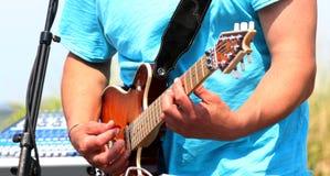 Bemannen Sie das Spielen einer E-Gitarre draußen in einer blauen Grafschaft lizenzfreie stockbilder