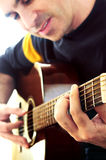 Bemannen Sie das Spielen einer Gitarre Stockfotos