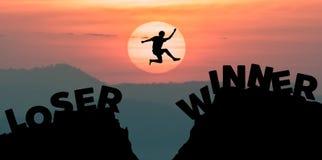 Bemannen Sie das Springen über Abgrund zwischen zwei felsige Berge bei Sonnenuntergang lizenzfreies stockbild