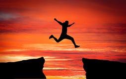 Bemannen Sie das Springen, über den Abstand von einem Felsen, zum dem anderen anzuhaften Stockfotografie