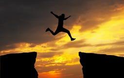 Bemannen Sie das Springen, über den Abstand von einem Felsen, zum dem anderen anzuhaften Stockfotos