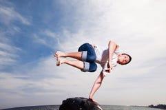 Bemannen Sie das Springen auf den Strand auf Himmelhintergrund Stockfotografie