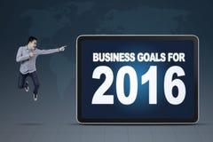 Bemannen Sie das Springen beim Zeigen auf Unternehmensziele für 2016 Stockfoto