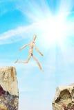 Bemannen Sie das Springen vom einem Felsen zu anderen über Abgrund Stockbilder