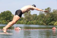 Bemannen Sie das Springen weg vom Sprungbrett am Swimmingpool Lizenzfreie Stockbilder