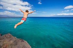 Bemannen Sie das Springen weg von der Klippe in den Ozean Stockfotografie