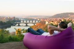 Bemannen Sie das Stillstehen in einem aufblasbaren Sofa bei Sonnenaufgang Lizenzfreie Stockfotos