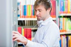 Bemannen Sie das Suchen nach einem Buch im Regal auf einer Bibliothek Stockbilder