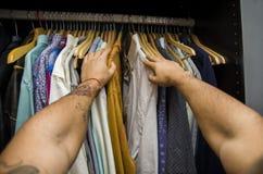 Bemannen Sie das Suchen nach einem Hemd in seiner Garderobe Stockfoto