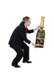 Bemannen Sie das Tragen einer übergroßen Champagnerflasche Lizenzfreies Stockfoto