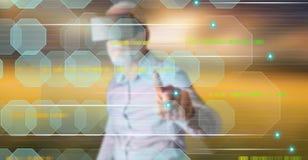 Bemannen Sie das Tragen eines virtuellen Kopfhörers der Wirklichkeit, der ein abstraktes Technologiekonzept auf einem Touch Scree Lizenzfreie Stockfotos