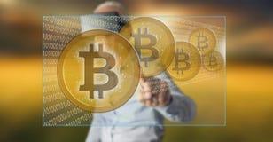 Bemannen Sie das Tragen eines virtuellen Kopfhörers der Wirklichkeit, der ein bitcoin Währungskonzept auf einem Touch Screen berü Stockfotos