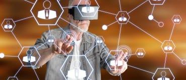 Bemannen Sie das Tragen eines virtuellen Kopfhörers der Wirklichkeit, der ein Soziales Netz auf einem Touch Screen berührt Lizenzfreies Stockfoto