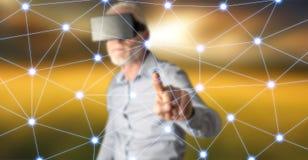 Bemannen Sie das Tragen eines virtuellen Kopfhörers der Wirklichkeit, der ein virtuelles Netz auf einem Touch Screen berührt Lizenzfreie Stockbilder