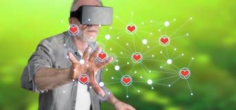 Bemannen Sie das Tragen eines virtuellen Kopfhörers der Wirklichkeit, der ein virtuelles Soziales Netz auf einem Touch Screen ber Lizenzfreie Stockfotos