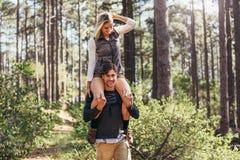 Bemannen Sie das Tragen seines Frauenpartners auf seinen Schultern während Trekking I stockfotos