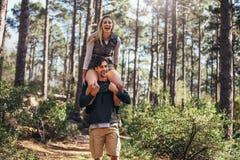 Bemannen Sie das Tragen seines Frauenpartners auf seinen Schultern während Trekking I lizenzfreie stockbilder