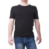 Bemannen Sie das tragende leere schwarze T-Shirt, das auf weißem Hintergrund mit Kopienraum lokalisiert wird T-Shirt Design und L Stockfotografie