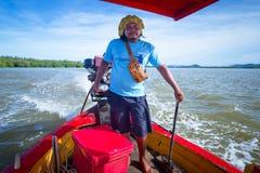 Bemannen Sie das Transportieren der Leute auf dem Boot über dem Fluss Lizenzfreies Stockfoto