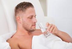Bemannen Sie das Trinken eines Glases Wassers im Bett Lizenzfreie Stockfotos
