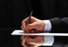 Bemannen Sie das Unterzeichnen eines Dokuments oder das Schreiben der Korrespondenz mit einem Abschluss herauf Ansicht seiner Han stockbilder
