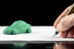 Bemannen Sie das Unterzeichnen eines Vertrages für ein grünes eco Auto Lizenzfreie Stockfotos