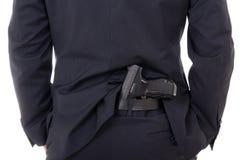 Bemannen Sie das Verbergen des Gewehrs in den Hosen hinter seinem zurück lokalisiert auf Weiß Stockfotos