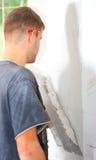 Bemannen Sie das Vergipsen der Wand stockfoto
