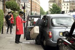Bemannen Sie das Verschalen eines Taxis außerhalb eines Hotels in London stockfotos