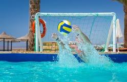 Bemannen Sie das Versuchen, den Ball im Pool zu fangen, das Wasserball spielt stockfotografie