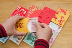 Bemannen Sie das Vorbereiten einer roten Tasche für chinesisches neues Jahr Lizenzfreies Stockfoto