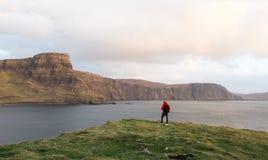 Bemannen Sie das Wandern durch schottische Hochländer entlang schroffer Küstenlinie Stockbilder