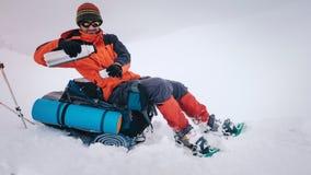 Bemannen Sie das Wandern mit Rucksack und Schneeschuhen im Winterberg Stockfotografie