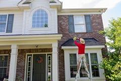 Bemannen Sie das Waschen der Laibungen oder der Dachgesimse eines modernen Hauses lizenzfreie stockfotos