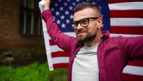 Bemannen Sie das Wellenartig bewegen einer US-Flagge beim Gehen entlang die Straße - das Konzept des Unabhängigkeitstags USA Lang stock video footage