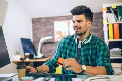 Bemannen Sie das Zahlen mit Kreditkarte auf Computer im Büro Stockfotografie