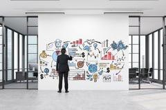 Bemannen Sie das Zeichnen eines Geschäftsplakats in einem Korridor mit treffendem roo zwei Stockfotografie