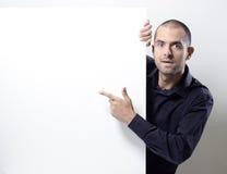 Bemannen Sie das Zeigen auf eine leere Anschlagtafel auf Weiß Lizenzfreie Stockfotos