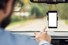 Bemannen Sie das Zeigen auf leeren Smartphoneschirm im Autowindschutzscheibenhalter Stockfotografie
