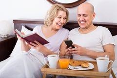 Bemannen Sie das Zeigen Freundin etwas auf Buch während des Frühstücks Lizenzfreie Stockfotos