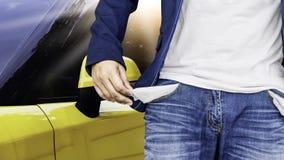Bemannen Sie das Zeigen seiner leeren Taschen mit gelbem Autohintergrund Stockfotografie
