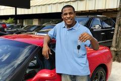 Bemannen Sie das Zeigen von Taste des neuen roten Sportautos Lizenzfreie Stockfotografie