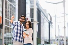 Bemannen Sie das Zeigen während die Frau, die digitale Tablette außerhalb des Gebäudes verwendet Lizenzfreie Stockfotos