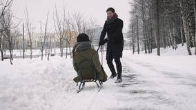 Bemannen Sie das Ziehen des Mädchens auf einem Schlitten am Schnee stock video footage