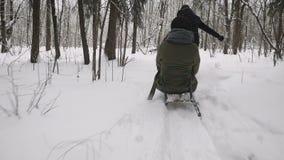 Bemannen Sie das Ziehen des Mädchens auf einem Schlitten am Schnee Antreiben in einen Schlitten stock video footage