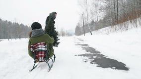 Bemannen Sie das Ziehen des Mädchens auf einem Schlitten am Schnee Antreiben in einen Schlitten stock footage