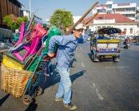 Bemannen Sie das Ziehen eines Warenkorbes, der mit houswares Kreuzen eine verkehrsreiche Straße in Bangkok geladen wird Lizenzfreie Stockbilder