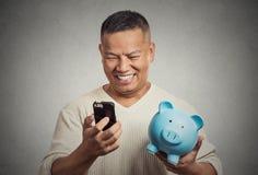 Bemannen Sie den Angestellten, der das Sparschwein hält, das intelligentes Telefon betrachtet Lizenzfreie Stockfotos